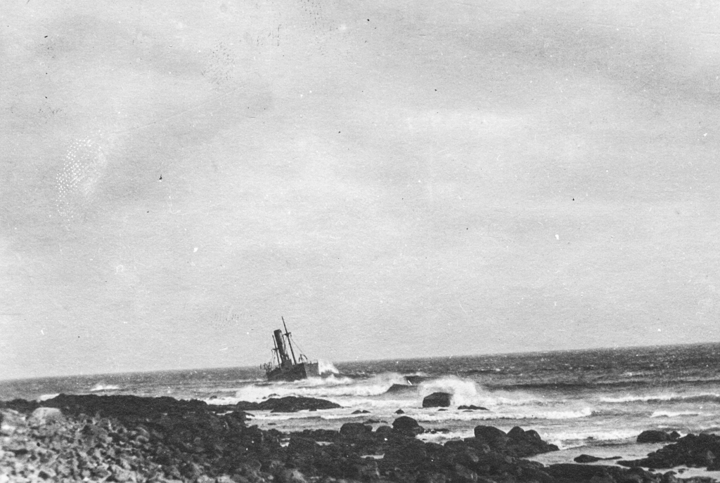 Black and white archival photograph of large passenger liner ship, the SS Florizel, run aground just offshore from rocky beach.