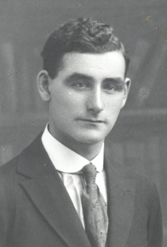 Black and white archival photograph of a man in a suit and tie.
