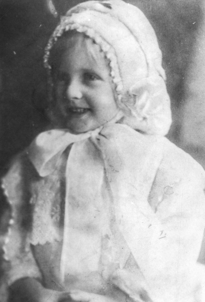 Black and white archival photograph of a girl wearing a white bonnet tied in a bow under her chin and a white dress.