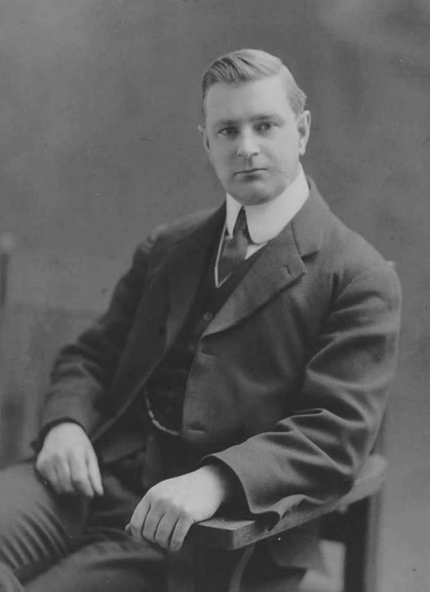 Black and white archival photograph of man seated in chair wearing a suit, and tie.