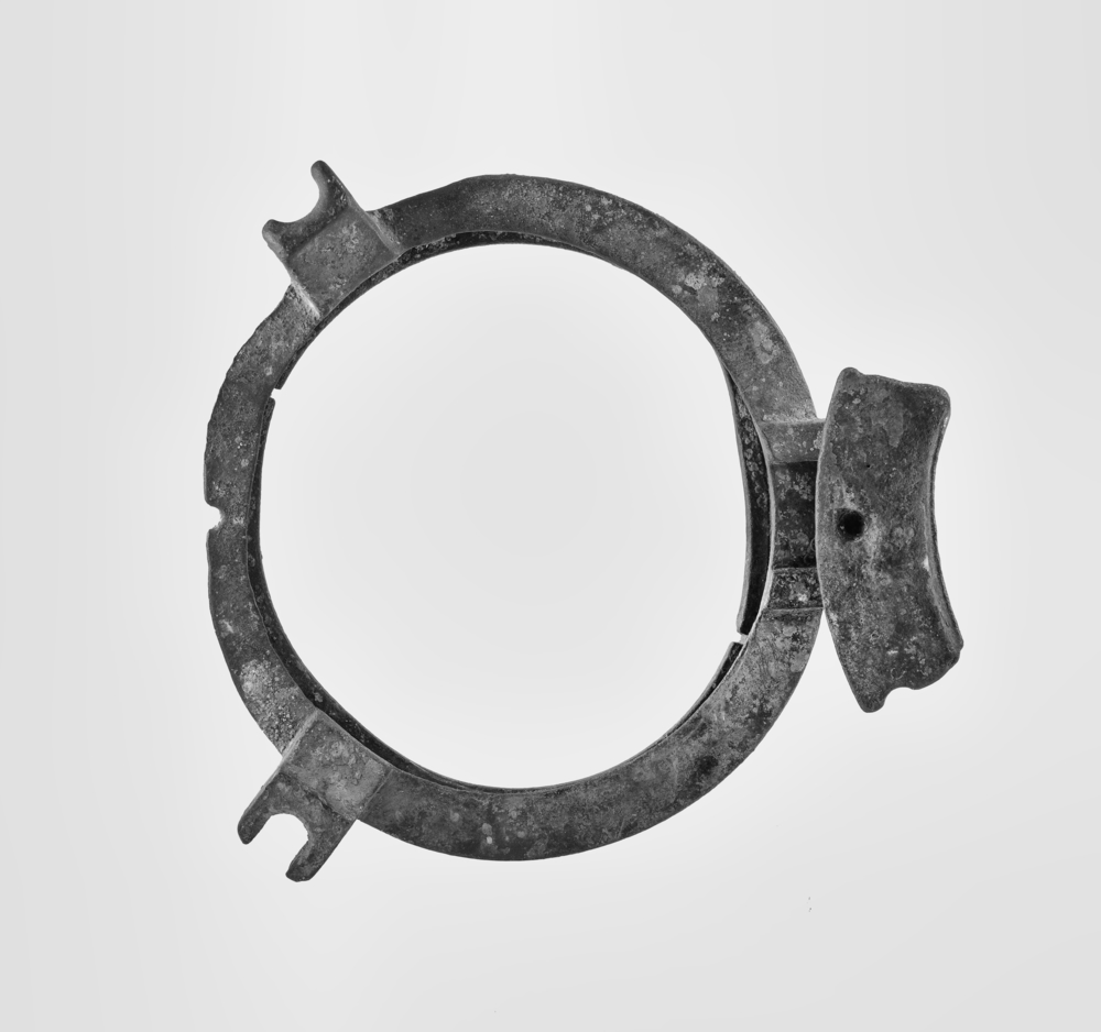Black and white modern photograph of porthole. Metal circle with hinge to the right hand side.
