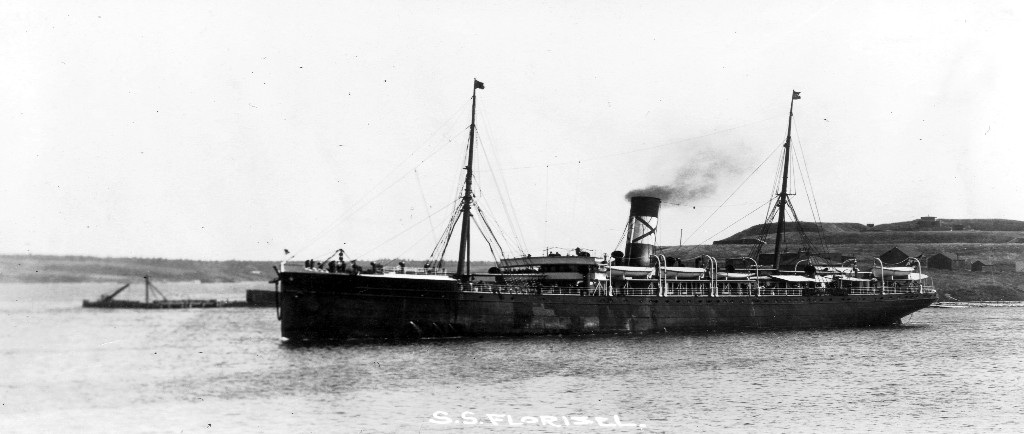 Black and white archival photograph. Large passenger liner ship, the SS Florizel, in a harbour. Behind ship to the right there are homes located on a hill, to the left there is a wharf.
