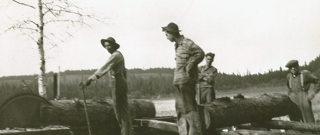 Four men are working beside a primitive sawmill. The saw is cutting a large Larch log and another large log is on the carriage waiting to be cut. The sawmill is in an open field.