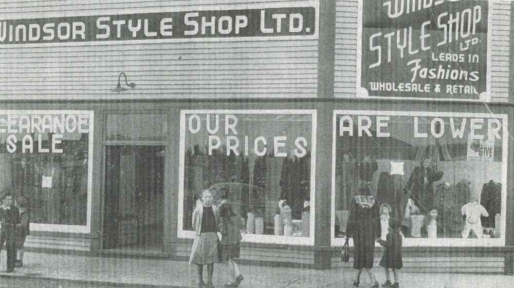 Black and white archival photograph. Street view. Window signs from left to right read: CLEARANCE SALE OUR PRICES ARE LOWER. Sign on the right side of the building reads: WINDSOR STYLE SHOP LTD. LEADS IN Fashions WHOLESALE & RETAIL. Six people stand on the sidewalk outside the building. Two boys, two girls, and a mother and daughter.