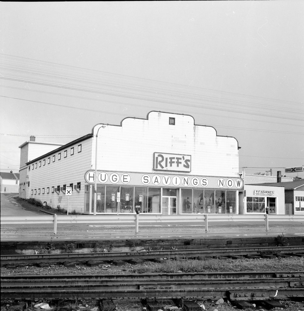 Black and white archival photograph. Street view. Building visible across railway tracks. Sign across building reads RIFF'S and below that HUGE SAVINGS NOW. Male and female manikins are visible in the front windows. P.F. Kearney's shop is to the right.