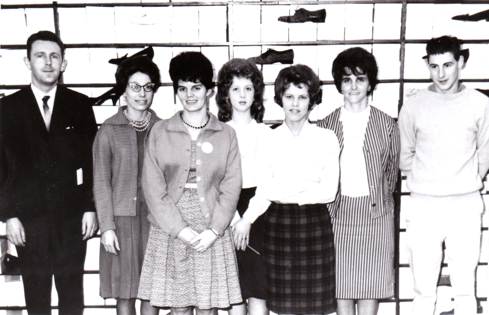 Black and white archival photograph. Staff in front of a wall of shoes. Left to right: man in a business suit with a tie, five women, and a man wearing a long sleeved shirt and pants. All people have dark hair. Women are all wearing skirts and shirts or dresses, and some wear blazers.