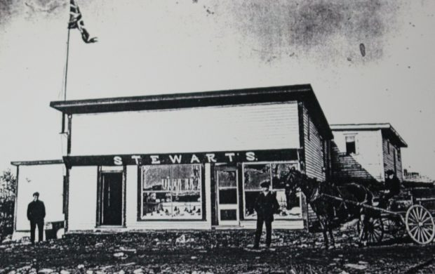 Black and white archival photograph. Street view. The main building has two entrance doors and two large windows. A union jack flies over the left side of building. There are two men standing outside, and another man driving a horse and cart.