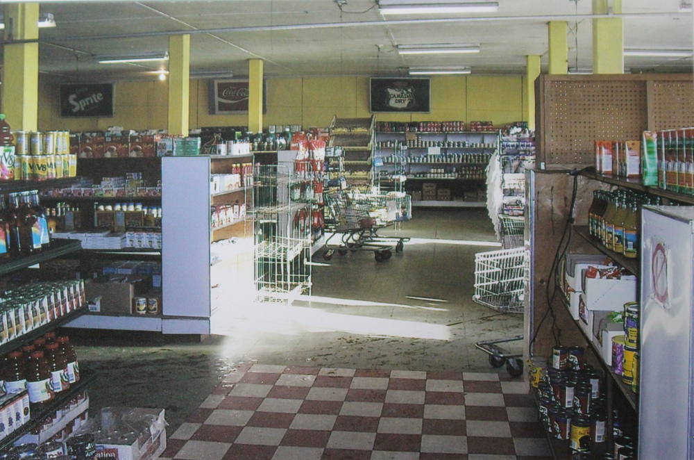 Colour photograph. Several shopping carts line the aisle, cans and bottles line the shelves, and the floor on the front right side is checkered red and white while it is beige in left and back portion of photo.