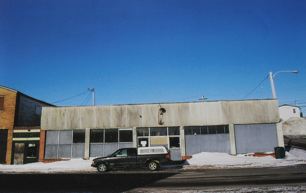 Colour photograph. Exterior view of Stewart's shop. This building was constructed in the 1950s following a fire on Main Street, Windsor. A truck is parked in front of the building.