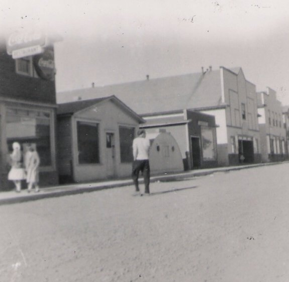 Black and white photograph. Street view. Main Street looking east. The small semicircular metal building third from the left is Stroud's chip van.