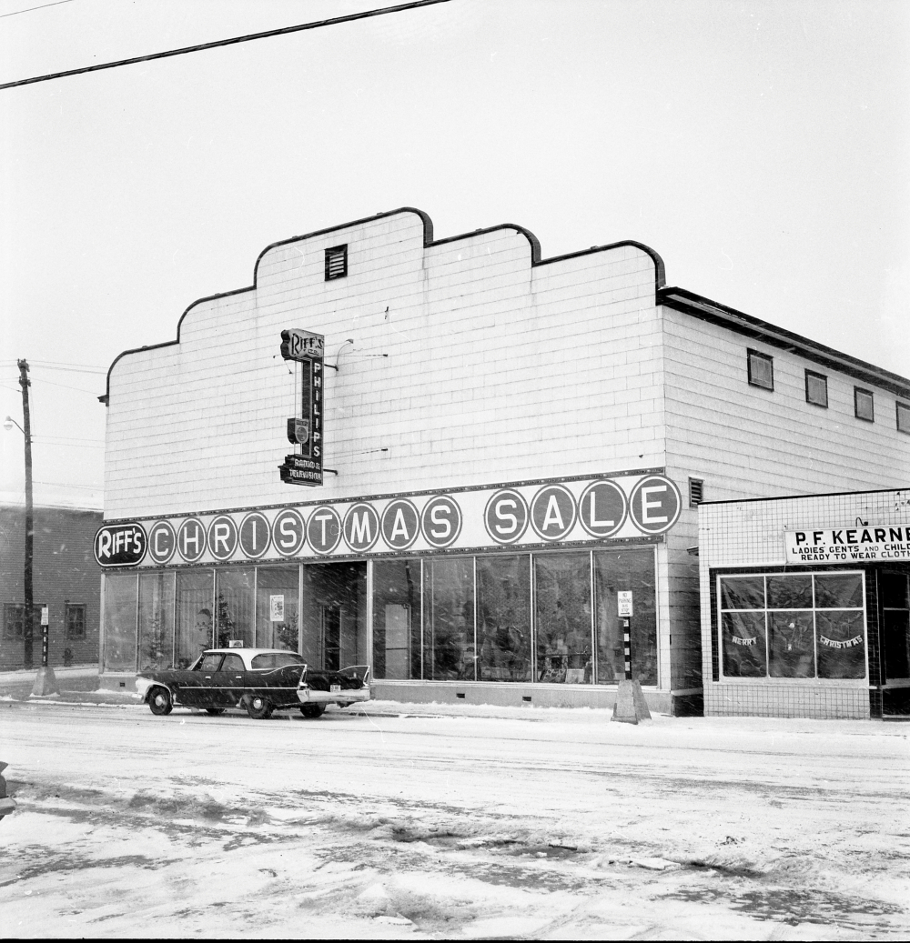 Black and white archival photograph. Street view. Exterior view of Riff's and P.F. Kearney's. Christmas décor can be seen in the windows of both shops. Snow is falling and there is a car parked in front of Riff's. The sign above Riff's says: RIFF'S CHRISTMAS SALE.