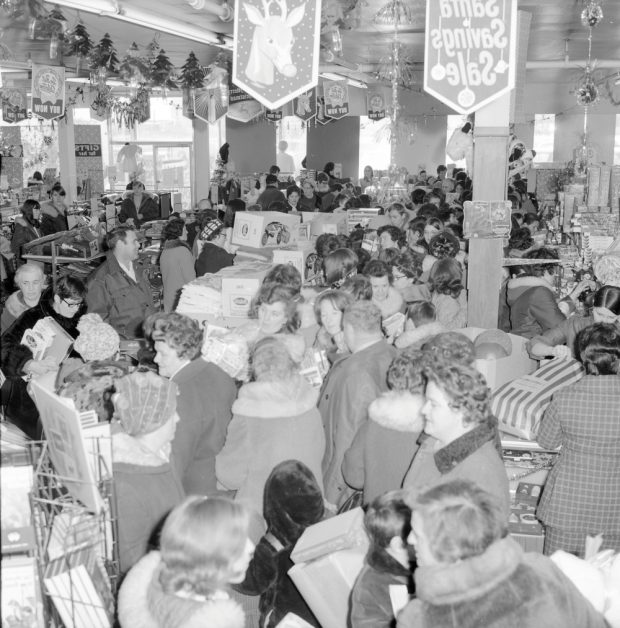 Black and white archival photograph. Over 70 people in winter coats and hats in line at Cohen's while Christmas decorations and banners hang from the ceiling.