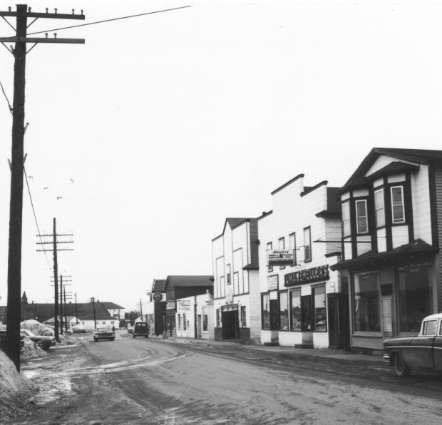Black and white archival photograph. Street view, Several Main Street businesses on right side. Left side of the street is lined with poles. St. Joseph's Parish visible in background on left side.