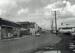 Black and white archival photograph. Street view. Main Street businesses on left side of photo, telephone poles and the railway station on right side. There are four cars on the street, and several pedestrians on the sidewalk in the left part of photo.