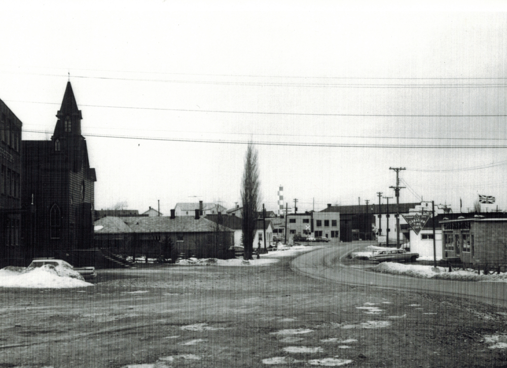 Black and white archival photograph. Street view. Looking north toward Main Street, Windsor from St. Joseph's Parish which is on the left side of photo. Canadian Tire Corp'n on right side. Railway crossing sign in the centre of the photo.