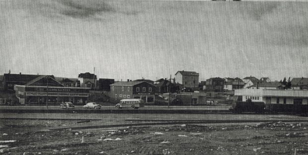 Black and white archival photograph. Street view. Railway tracks in foreground and stores in background. S. Cohen & Sons on left side, train and Newfoundland railway station on right side.
