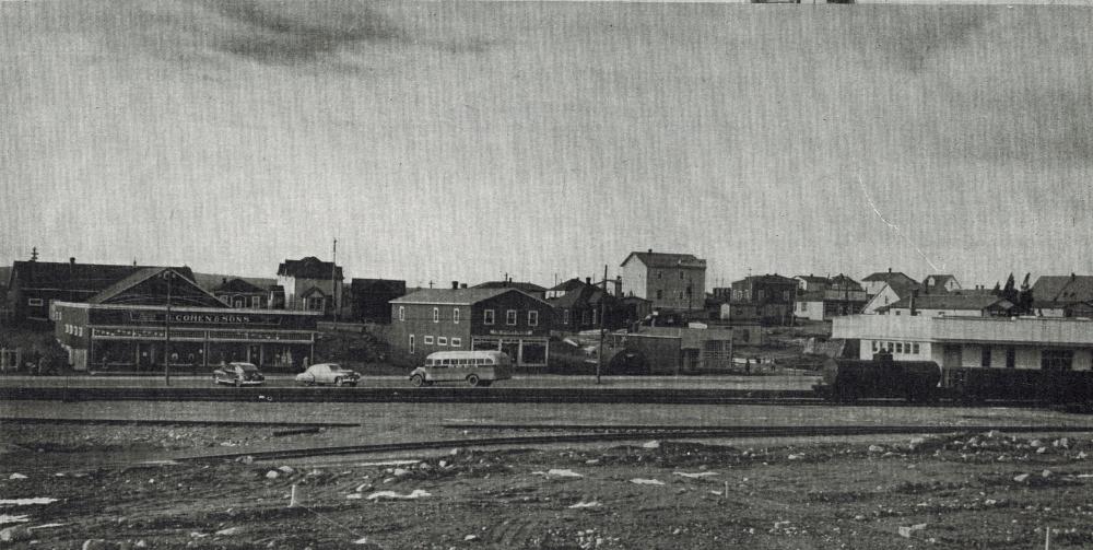Photographie d'archives en noir et blanc. Vue de la rue. Le chemin de fer au premier plan et magasins en arrière-plan. À gauche on voit le magasin S. Cohen & Fils, à droite le train et la gare du chemin de fer de Terre-Neuve.