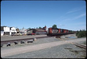 Colour photograph. Photo looking towards Main Street from behind railway tracks. CN train on right side and train station in the centre of the photo.