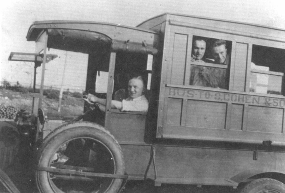 Photographie d'archives en noir et blanc. Un homme conduit un bus qui compte deux passagers à la première fenêtre. Sur le côté du bus est écrit : BUS TO S. COHEN & SONS (BUS VERS S. COHEN & FILS).
