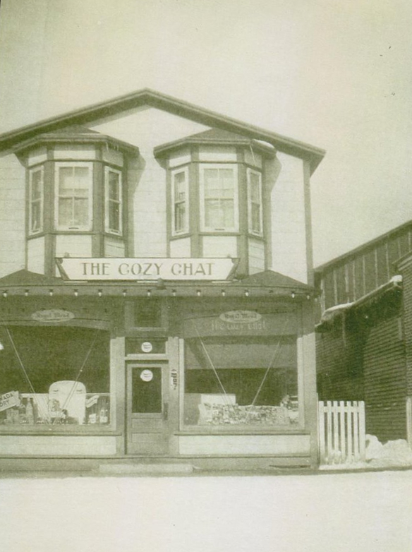 Black and white photograph. Exterior view of Cozy Chat. There are two bay windows on the second floor.