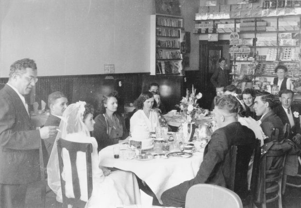 Black and white archival photograph. Wedding party of Florence Hollett and Jack Maloney seating around tables inside the Cozy Chat.