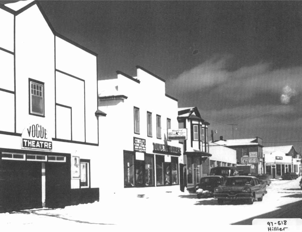 Black and white archival photograph. Street view. Connolly's Shoe Store and Tuma Jewellers in centre of photo to the right of Vogue Theatre.