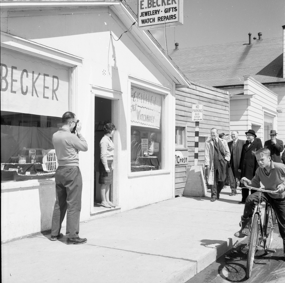 Black and white archival photograph. Street view. Exterior view of E. Becker. Man to the left of photograph taking a picture, woman stands in doorway, group of six men in suits walk towards the shop, and a boy rides his bicycle past shop.