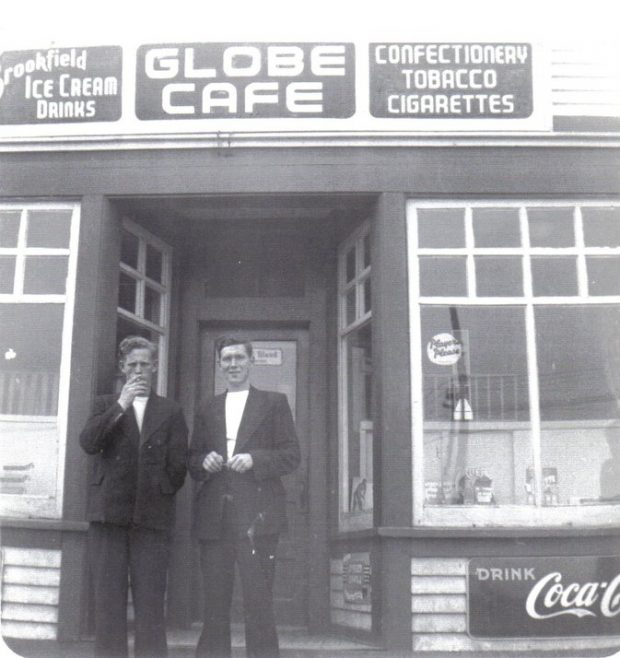 Black and white photograph. Two men standing on steps of the Globe Cafe between two bay windows. Signs on top of building from left to right read: Brookfield ICE CREAM DRINKS, GLOBE CAFE, and CONFECTIONERY, TOBACCO, and CIGARETTES. Bottom right sign says: DRINK Coca-Cola.