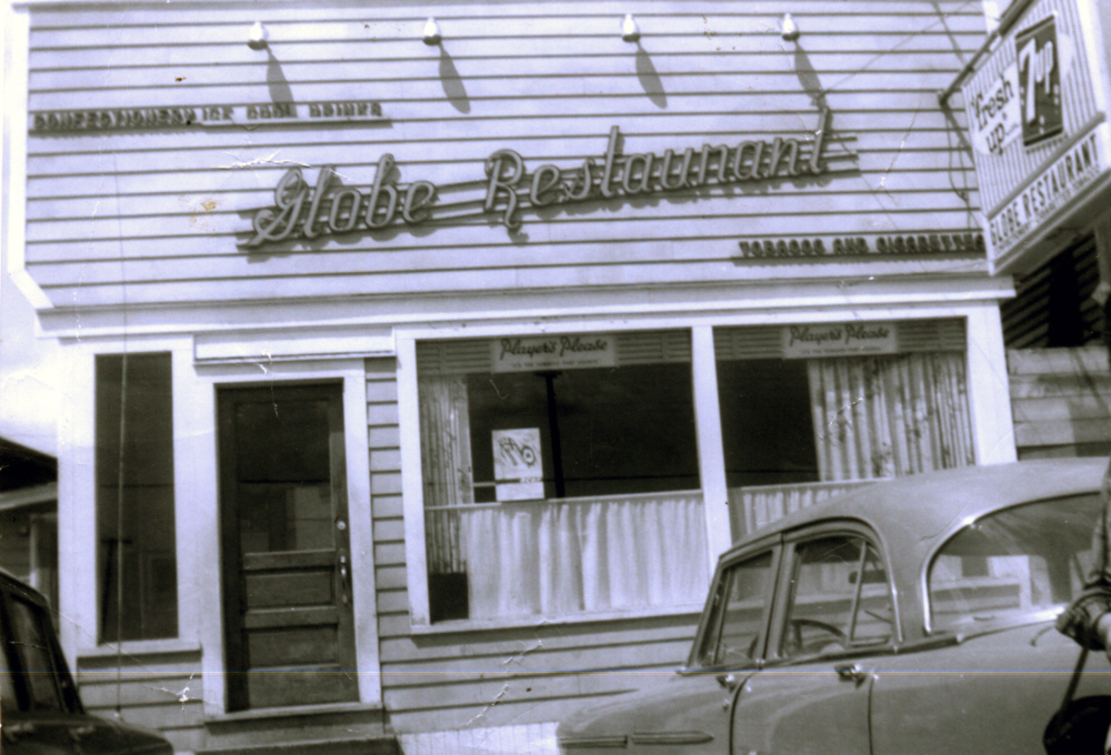 Black and white photograph. Two cars parked in front of the Globe Restaurant. Signs above the door from left to right read CONFECTIONERY ICE COOL DRINKS, Globe Restaurant, and TOBACCO AND CIGARETTES. Sign stating Players Please hung in both windows.