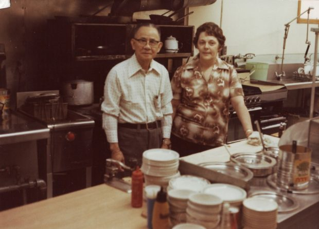 Colour photograph. Inside the Globe Restaurant kitchen. An oven is visible behind a man and woman are in the centre of the photo.