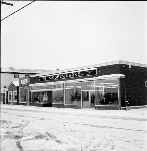 Black and white archival photograph. Street view. S. Cohen & Sons and Cohen's Furniture Department looking west on Main Street, Windsor. Sign above store reads: DRY GOODS; HARDWARE; FURNITURE; S. COHEN & SONS LTD.; WHOLESALE AND RETAIL. Female and male manikins visible in the store windows.