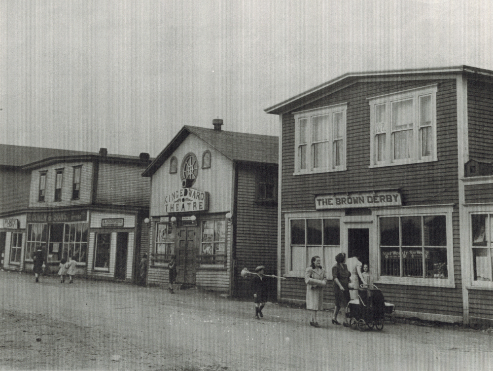 Black and white archival photograph. Street view. Looking west on Main Street, Windsor. Brown Derby, King Edward Theatre, A. Peckford, S. Cohen & Sons, and Purity Cafe visible. Kirk Pomeroy is carrying a birch broom, Daisy Bennett is wearing a light coat, and Mrs. Pomeroy is pushing a stroller.