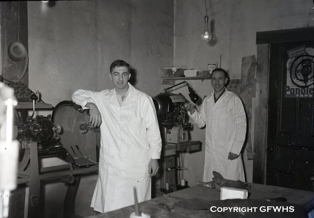 Black and white archival photograph. Two men in white lab coats stand in Hermann Münch's shoe shop.