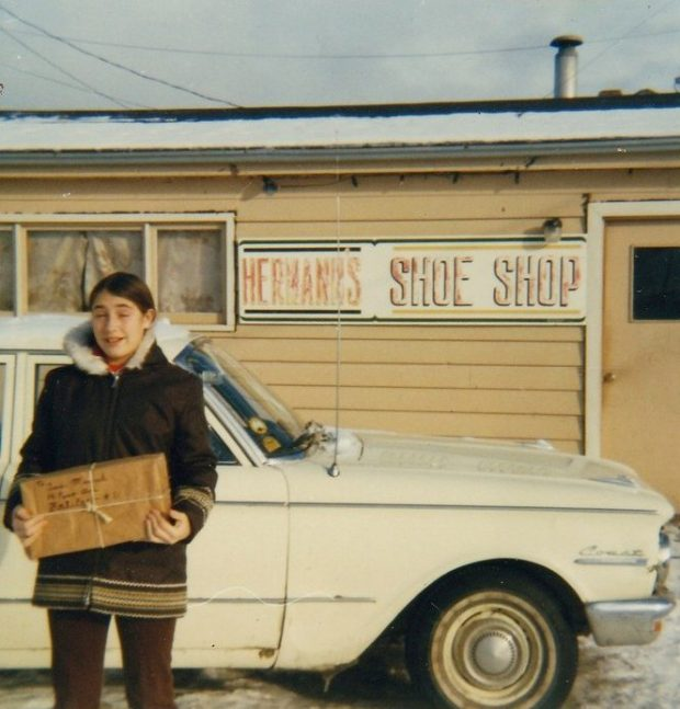 Colour photograph. Street view. Girl in a winter coat holding a package stands in front of a white car outside of Hermann's Shoe Shop,.