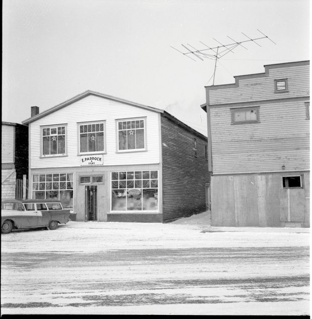 Black and white archival photograph. Street view. Exterior view of E. Paddock & Sons during the Christmas season. Decorative garland and stars can be seen in windows and there are toys displayed in the lower windows.