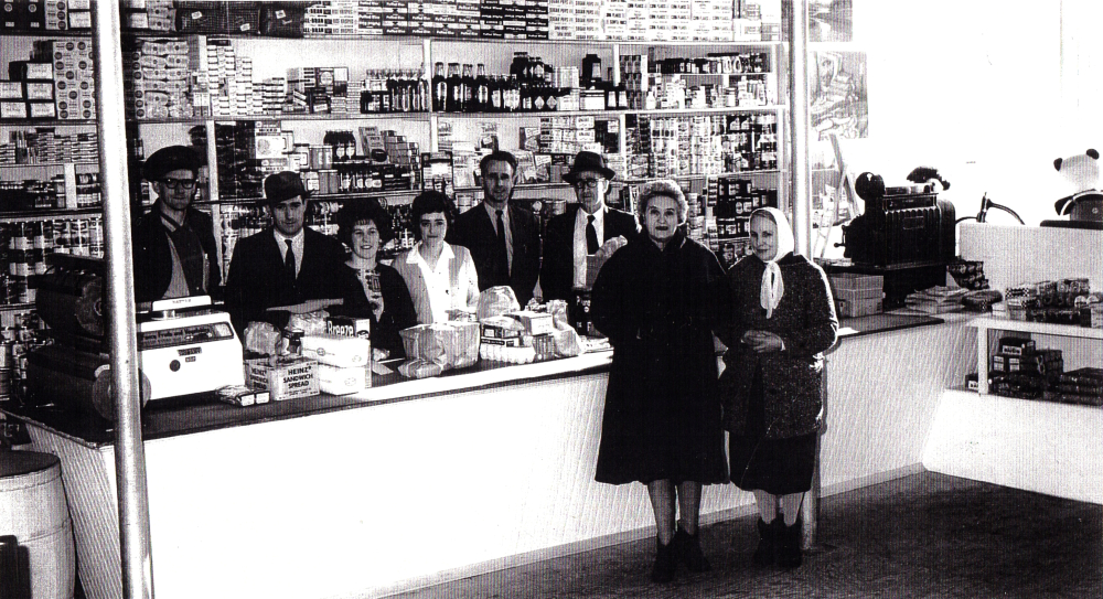 Black and white archival photograph. Four men and two women behind the cash register and counter, and two women in coats in front of the counter. The shelves behind the cash register and stocked full of packages, cans, and bottles of product.