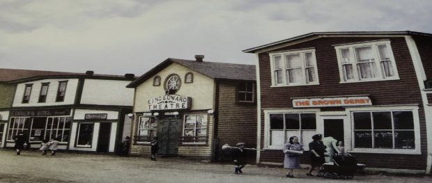 Colour archival photograph. Brown Derby, King Edward Theatre, A. Peckford, S. Cohen & Sons, and Purity Cafe. Kirk Pomeroy is carrying a birch broom, Daisy Bennett is wearing a blue-grey coat, and Mrs. Pomeroy is pushing a stroller.