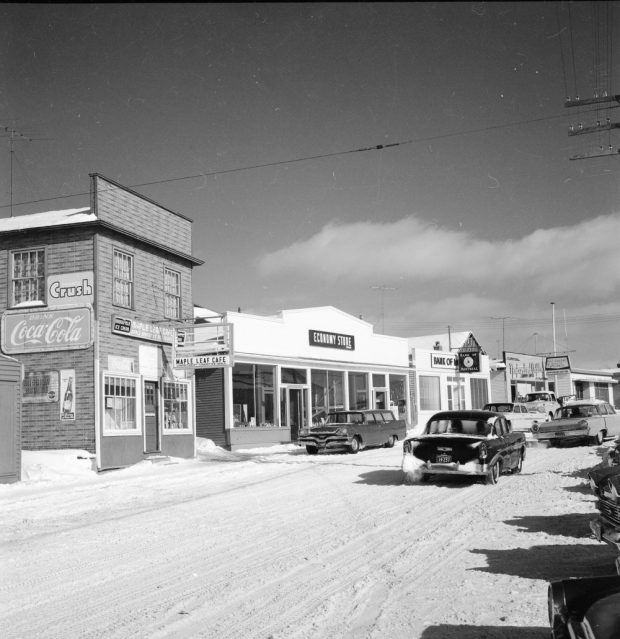 Black and white archival photograph. Street view. Maple Leaf Cafe, Economy Store, Bank of Montreal, Newfoundland Outfitting, and Windsor Post Office visible. Several cars are in the streets and there is snow on the ground.