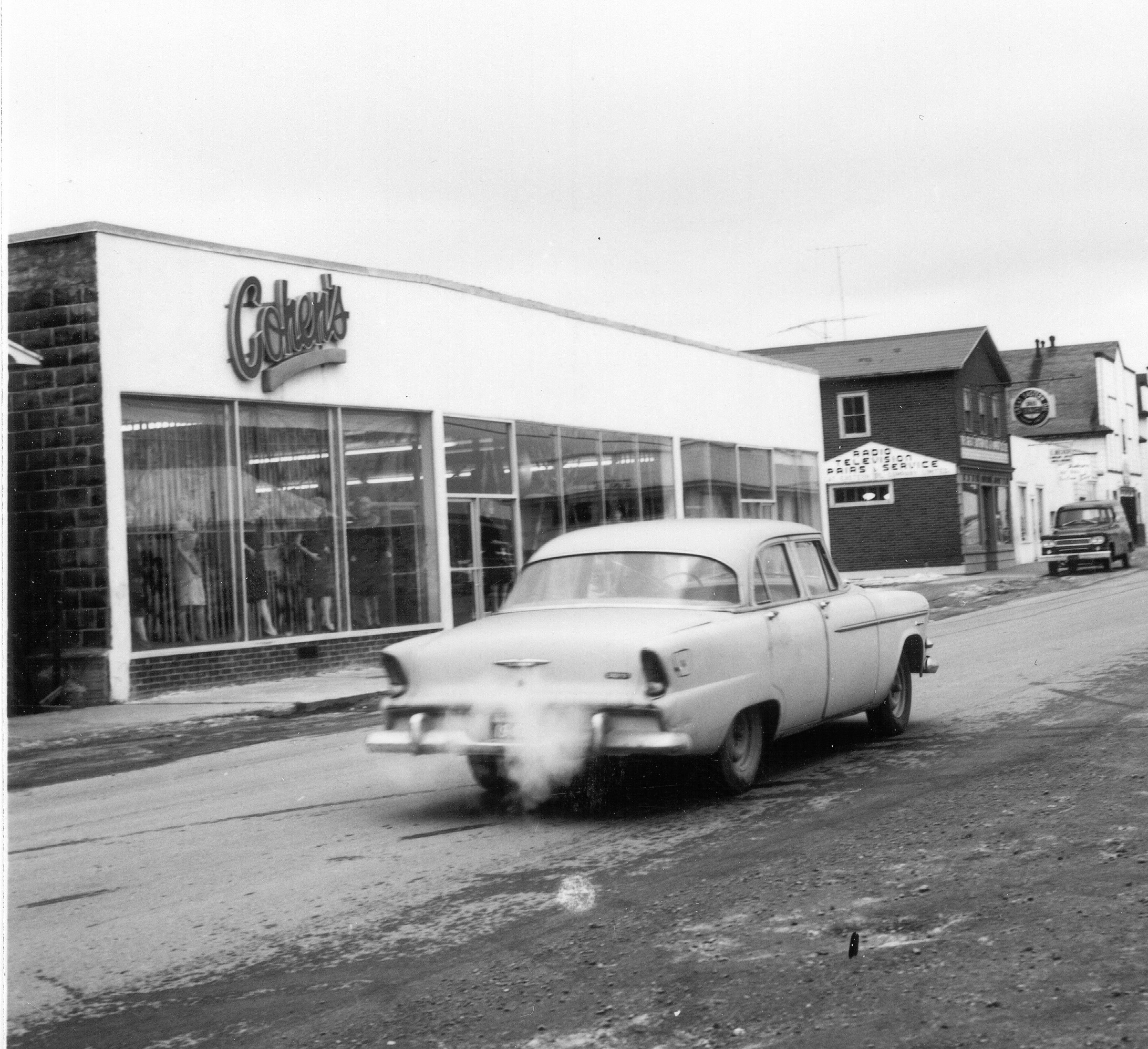 Black and white archival photograph. Street view. Cohen's, Main Street looking east towards Great Eastern Oil, and E. Becker's shop. Women's manikins visible in the windows on the left side of Cohen's main doors. Light car in the centre of the photo.