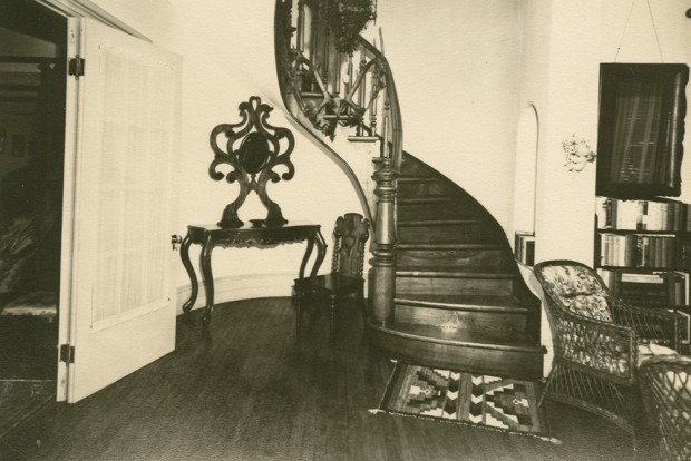 Back-and-white photograph of the entrance hall of Manoir Fraser with a wooden staircase in the centre.