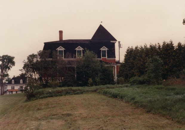Colour photograph. In the centre, an empty house. In the foreground, an overgrown yard.