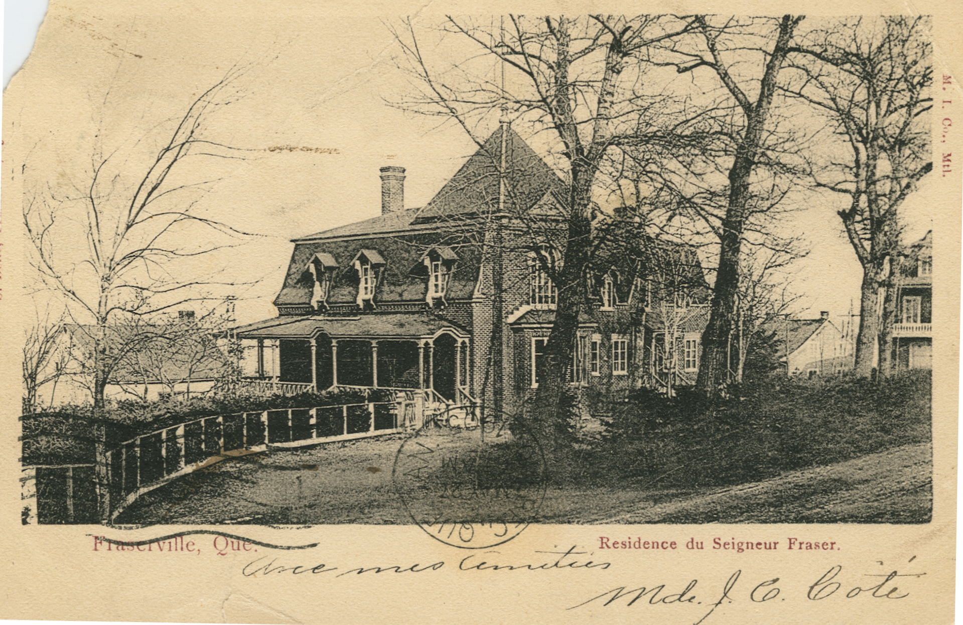 A black-and-white postcard showing a large elegant house with a veranda, bay window, and mansard roof. A few mature trees line the drive to the house.