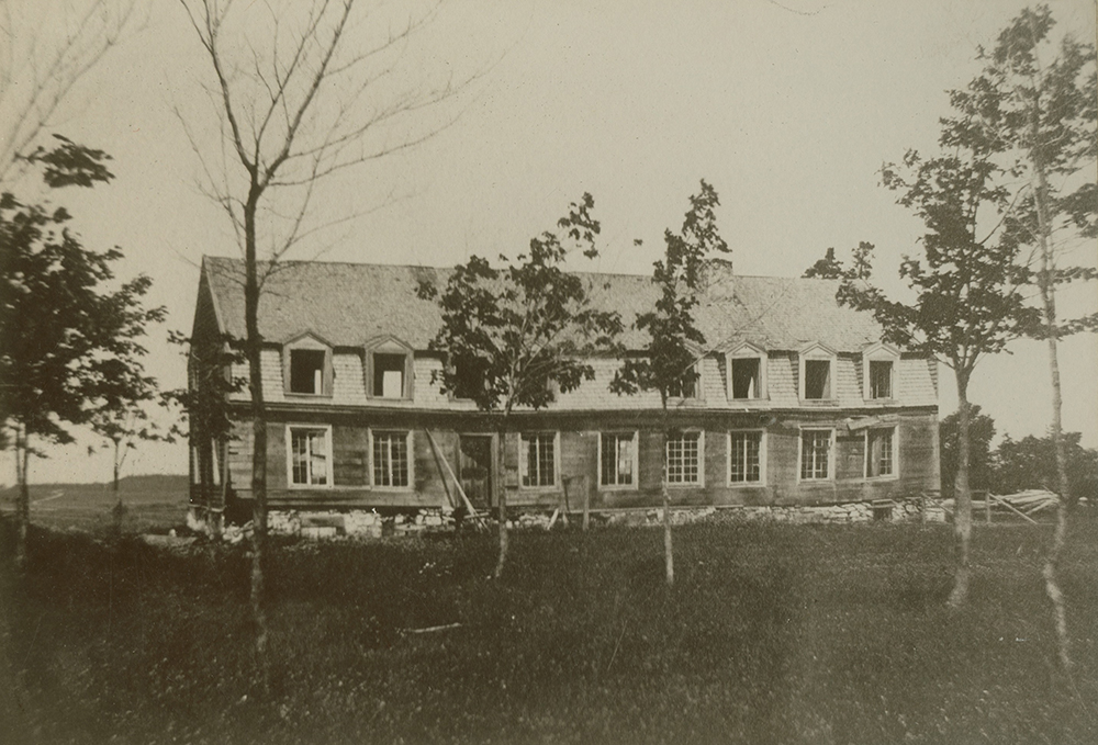 Black-and-white photograph of a long house, apparently empty. The mansard roof has many dormer windows.