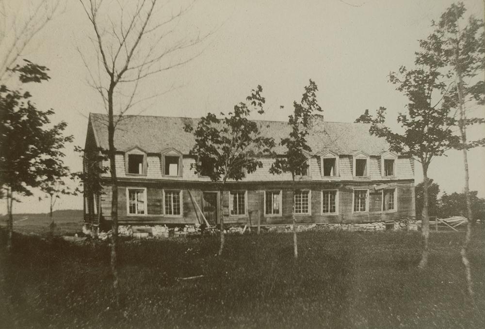 Photo noir et blanc. Longue maison abandonnée. Le toit mansardé est percé de nombreuses lucarnes.