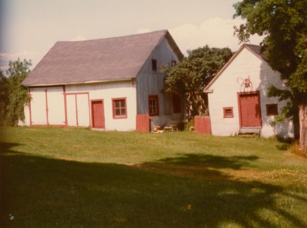 Colour photograph of two wooden buildings painted white. The doors and window frames are painted red.