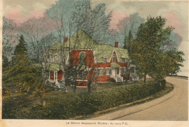 Colour image of a large brick house in winter behind a low cedar hedge and several trees.