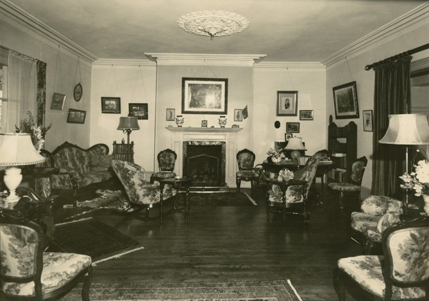 Black-and-white photograph of a crowded living room. The furniture is arranged along the walls on the right and left, and a fireplace is in the wall at the rear.