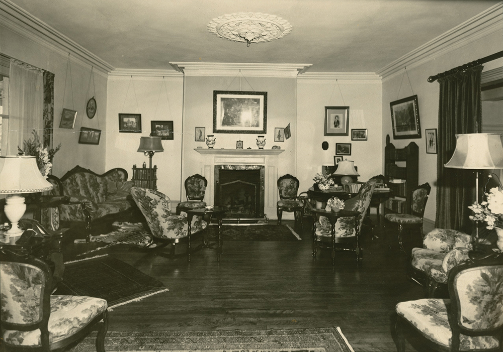 Charmant Black And White Photograph Of A Crowded Living Room. The Furniture Is  Arranged