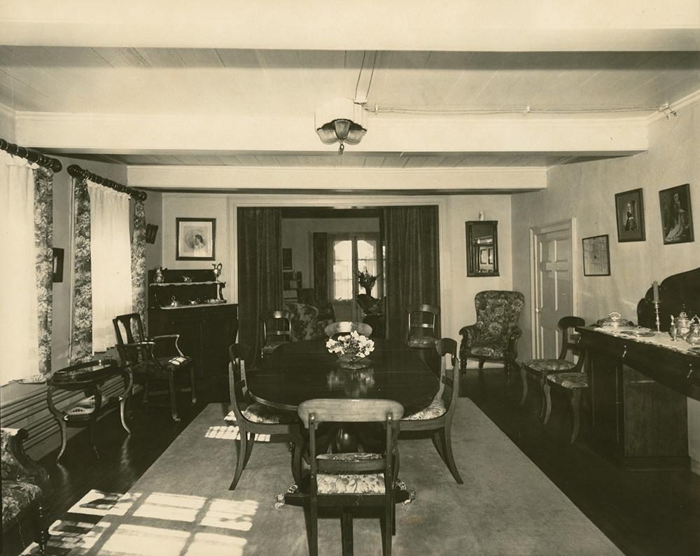 Photo noir et blanc. Salle à manger. La table est disposée au centre, sur un grand tapis. À gauche, un immense buffet est adossé au mur. On devine le salon en arrière-plan.
