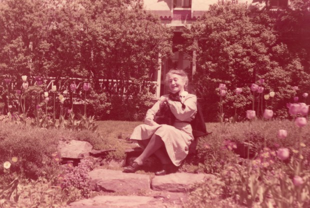 Colour photograph of an elderly woman sitting on steps in a flower garden.